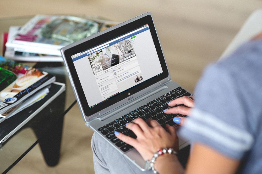 En kvinna som skapar engagerande Facebook-inlägg från sin laptop.