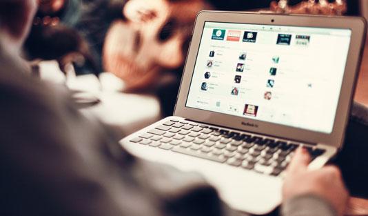 Person med en laptop, som visar hur hen jobbar med sökmotoroptimering av sin e-handel.