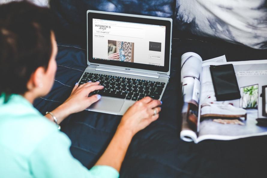 Kvinna med laptop som håller på att registrera ett domännamn.