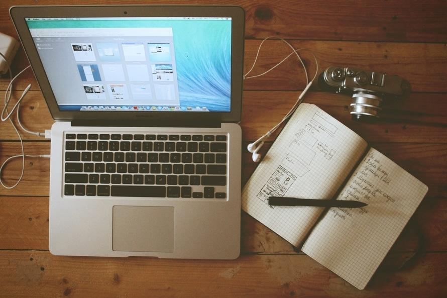 En laptop, en anteckningsbok och en kamera som kan ses som hjälpmedel för dig som vill marknadsföra ditt företag på nätet.
