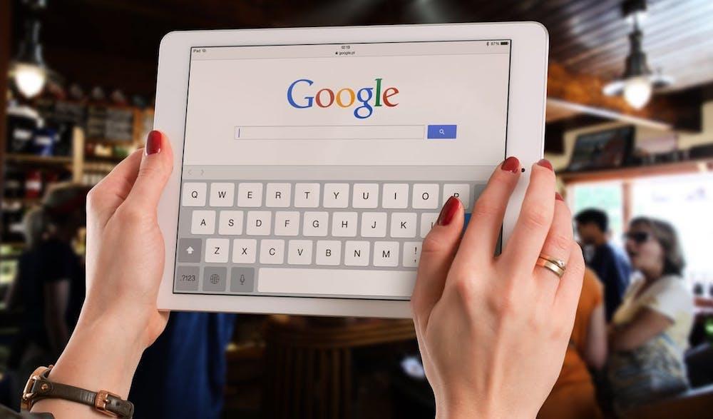 Kvinna håller i ipad som visar Google Sök