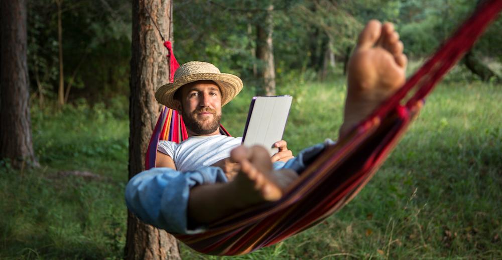 Man i hammock som ställer in ett autosvar på Loopia-mailen under semestern