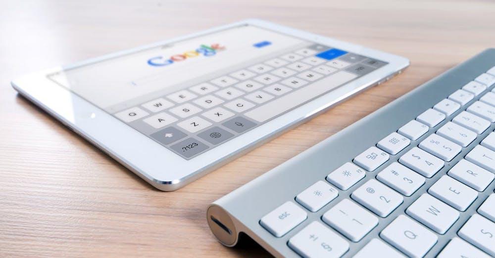 Ipad som visar Googles logotyp och ett tangentbord