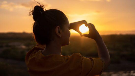 Kvinna som formar händerna som ett hjärta för att symbolisera kärleken till naturen för att stötta Earth Hour.