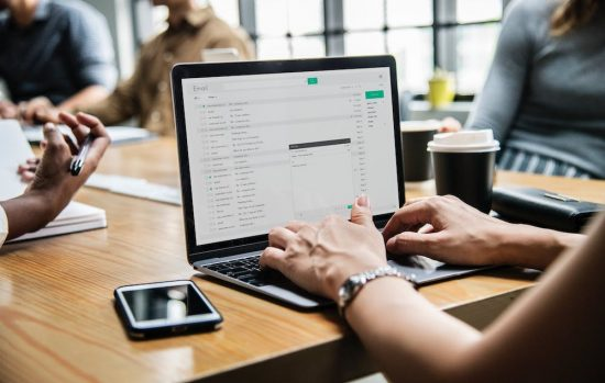 Kvinna läser och besvarar proffsig e-post med sin laptop som står på ett skrivbord